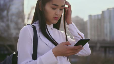 after school : School asian girls look on mobile phone. Woman has a school bag. Touching hair and typing message. Females serious, naughty and grumpy. Korean in Korea. Brunettes good student - text smart people.