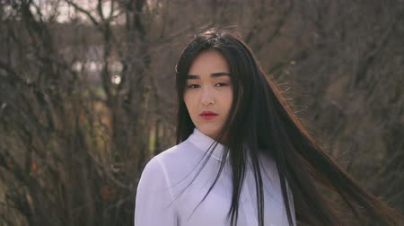 saç kremi : Asian teen turn to camera in slow mo. Female is graceful and sophisticated girl. Her hair flutters beautifully in the wind. Brunette turns with a serious proud face and looks straight into the camera.
