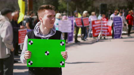 social inequality : Man near people on strike standing hold greenscreen banner. Empty poster with tracking points in persons hands. Demonstration in middle of day. Serious and sad guy with clear placard for copyspace 4k
