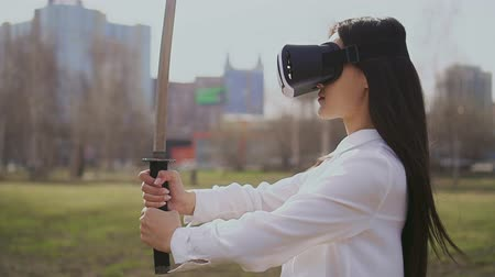 samuraj : Chinese girl looking at sword using virtual reality glasses. Wind blows on hair. Futuristic lady stands proudly and looks into the distance like a real warrior. Female is ready to attack her enemies. Wideo