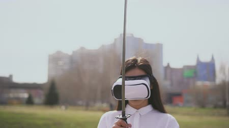 samuraj : Samurai woman playing vr game using real katana on fascinating green grass field. Female is seriouse while holding a sword. Being outside using digital equipment. Battle with warriors in simulation. Wideo