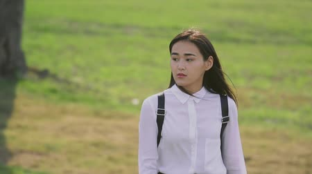 go to school : Pretty asian woman going on glade in slow motion and person straightening hair. Her shrewd gaze looks away, her lips parted slightly, models serious and unruffled. This is great shot to start a movie