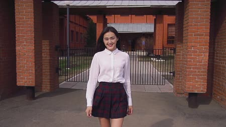 after school : Chinese people goes directly to camera smiling. Females hair is blown by slowmo. Girl smiles brightely and straightens her hair, which inflates with the wind in slow motion near brick wall of school. Stock Footage