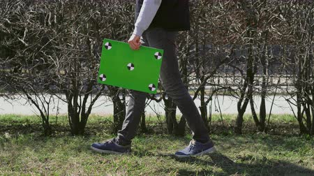 почтальон : Adult man walking near park and trees with green screen banner and look around. People hold chromakey table with track points. Guy going down street with empty board for copy space. Boy goes to work.