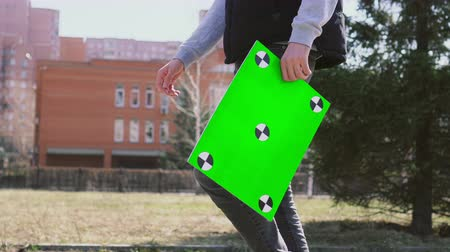legfőbb : Adult man walking near park and trees with green screen banner and look around. People hold chromakey table with track points. Guy going down street with empty board for copy space. Boy goes to work.