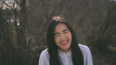 歯を見せる : Cute japanese teen laughing in forest and show all teeth. People enjoy good life. Girl stands among nature in a light school uniform. Beauty is relaxed, happy with her life. Lady is glad to everything