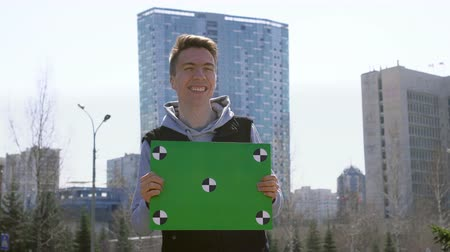 alku : Young man is standing near city and holding greenscreen banner. Empty poster with tracking points in boys hands. Guy is running an ad campaign. Happy and nice guy with clear placard for copyspace 4k Stock mozgókép