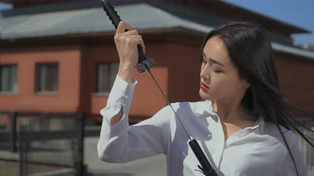 samuraj : Asian beauty pulls gorgeous sword out of its scabbard and looks at it adoringly. Wind blows the girls hair. Woman prepares for battle and checks the weapon for readiness for fighting. House is nice.