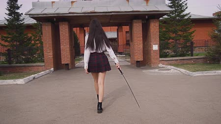 porażka : Beautiful schoolgirl walks proudly in slow motion scratching road with a katana. Girl going to the temple with the katana down and prepares to turn around and violently defeat her worst ninja enemies