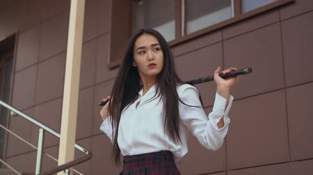 zabiják : Japanese people coming down the stairs in slow mo holding a sword in her hands. Girl pathetically descends the steps, slowly turning her head to the side. Attractive woman posing for fashion magazine. Dostupné videozáznamy