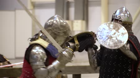 zbroja : Middle Age Teutonic Knight Battle Exibition Center. Medieval Soldier Wearing Protective Armor, Chain Mail and Helmet Fight with Sword and Shield. Brutal Game Footage Shot Full HD 1080p
