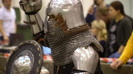 kuşatma : Medieval Knight Historic Battle Exibition Center. Man Wearing Vintage Protective Metal Armor. Warrior in Helmet Fighting with Sword and Shield for Audience Footage Shot Full HD 1080p