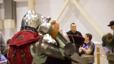 kuşatma : Middle Age Knight Perform Battle Convention Center. Medieval Man in Metal Armor, Helmet Fight with Sword and Shield Slowmotion. Knighthood Chivalry Performance Footage Shot in 4K (UHD) Stok Video