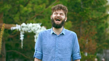 vendég : Kinky handsome man in a blue shirt is laughing at the top of his friends joke. Person is stylish and well dressed. Guy is standing on the background of green nice forest and beautiful white flowers.