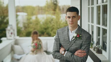 casar : Insanely handsome groom stands on the terrace with an important view. He is going to marry. Right behind him his beautiful wife sits on a bench. The girl has a bouquet of fragrant flowers in her hands Vídeos