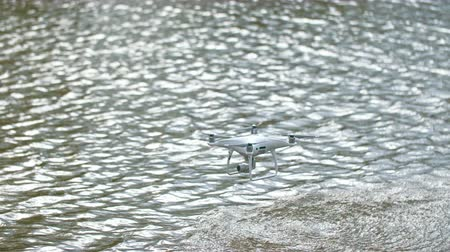 remotely : Quadcopter is flying over the water surface. Drone ripples over beautiful lake. Air robot held above water with help of small mechanisms. This device remotely controlled and can shoot landscape around