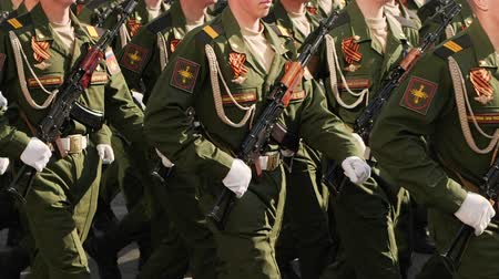 gururlu : Parade military men demonstrate army rifles closeup slow mo step into rhythm. platoon military army marche street slowmotion. Soldier army uniform with machine gun hand close up marching formation
