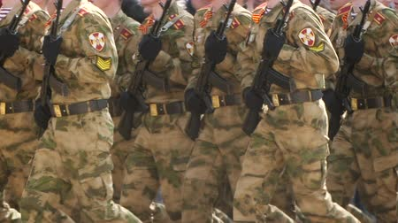 hodnost : Soldier army uniform with machine gun hand close up marching formation. platoon military army marche street slowmotion. Parade military men demonstrate army rifles closeup slow mo step into rhythm.