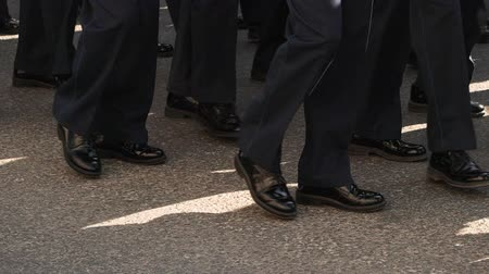 daily : Male legs close up in shoes go synchronously slow motion to work. The steps of men in trousers are clone leg on the road of the city. On the sidewalk feet marching closeup in the mass of the crowd Stock Footage