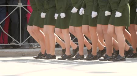 propaganda : Military women march in parade in green uniform in slow motion the town square. Close-up of a female march shoes a clone of steps on the road. Feminism building women in the parade of victory