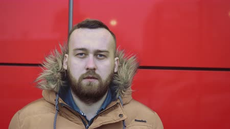swirling : Closeup people with beard turn head look the camera near red wall keying. handsome guy bristles look at camera around. Portrait man and his eyes in the street against the wall with a red background. Stock Footage