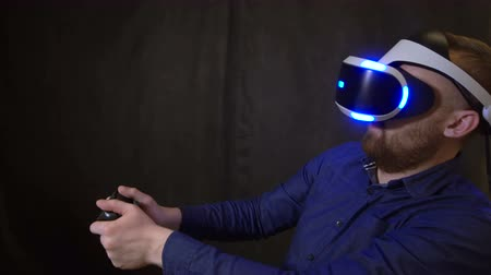 schrikken : The guy was sitting at the game in horror and rebounds from fear. People in virtual reality helmet closeup scared by the horror of the game with joystick in his hands 4K. Person inside digital reality