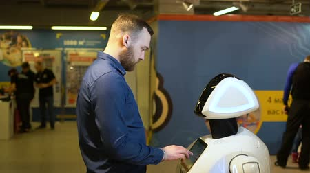 hitech : Man cyber exhibition of robot is studying, use white android working interface for question. Revolutionary progress in field of cybernation, robotization in demonstrating people of all possibilities