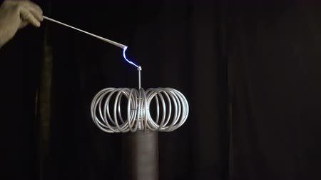 magnetisme : Current line coil sparkles rumble thunder random. man hand metallic part Tesla coil create blue electric arc spark black background 4K. experiment physic static electricity current flow through coil Vidéos Libres De Droits