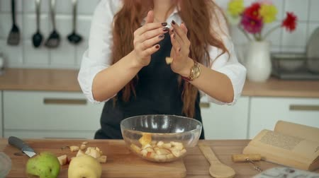 pears : Woman Stand at Cooking Counter at Domestic Kitchen. Closeup View of Girl Hands Dropping Chopped Pear Slices in Glass Bowl Slow Motion. Dessert from Recipe Book Preparation. Footage Shot in 4K