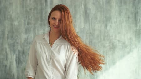 shake hair : Caucasian Young Woman Moving Ginger Hair Posing. Smiling Redhead Slightly Turns on Grey Wall Background Slowmotion. Carefree Female Model in White Shirt Looking an Camera. Footage Shot in 4K