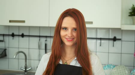 ruivo : Attractive Happy Woman at Modern Kitchen Closeup. Redhead Caucasian Girl Wearing Apron Looking at Camera with Cheerful Smile Slowmotion. Charming Lady Hostess. Footage Shot Full HD 1080p
