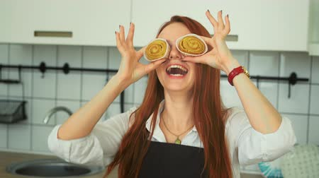 koláč : Happy Redhead Woman Having Fun at Home Kitchen. Carefree Housewife in Apron making Pie Glasses Closeup. Caucasian Girl Jumping Laughing while Cooking with Smile. Footage Shot Full HD 1080p