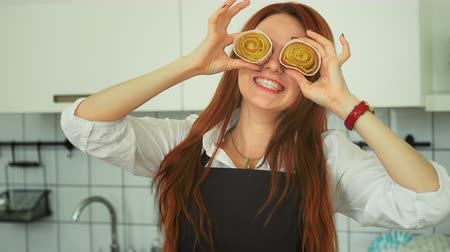culinária : Pretty Ginger Woman Having Fun at Domestic Kitchen. Smiling Girl Covering Eyes with Cinnamon Rolls. Sweet Dessert. Closeup Beauty Fool Around with Pie at Home. Footage Shot Full HD 1080p