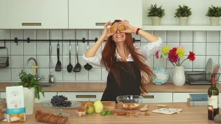 culinária : Playful Caucasian Girl Having Fun at Cozy Kitchen. Smiling Woman Covering Eyes with Cinnamon Rolls. Redhead Beautyful Hostess in Apron Playing with Pie, Jumping at Home. Footage Shot Full HD 1080p Stock Footage