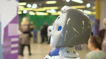 champ opératoire : Female robot demonstrates the progress of new digital technologies in the field of cyborgs. A human android walks around the exhibition hall, showing technological opportunities for new investors.
