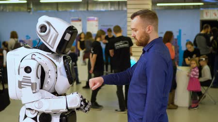 кулак : Robot cyber exhibition make gesture with man to beat off fist 4K. Demonstration of new technologies in cyber development for human life. Artificial intelligence show friendship with person in showroom