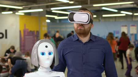 погружение : The man in glasses of virtual reality and the female robot are connected to the same network of new artificial intelligence technologies. At a cyber exhibit, a guy sees a cyborg through a helmet vr. Стоковые видеозаписи