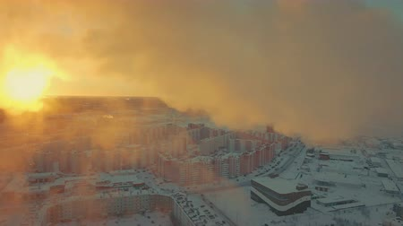 tanımlayıcı : Winter vapor spreads near setting sun, the rays gently pass through the clouds. Shooting from a quadrocopter shows all the beauties and the dangers of heat and power plant. Landscape is breathtaking Stok Video