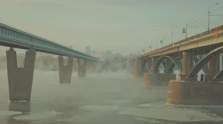 taxi : Two bridges stand side by side on river full of steam. The foggy city is very beautiful. A magical country with scenery is represented by curious look. Stone landscape underlines charm of road bridge.