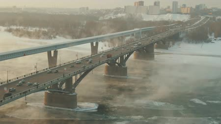 secretário : In a winter city, an impressive bridge rises above an ice-covered steamy river. Stone landscape of the Netherlands underlines the charm of road bridge, as if flying over a river. Bridge seems to soar. Stock Footage