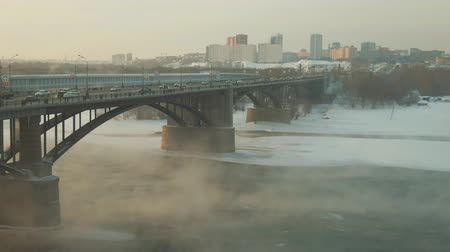 подвесной : Steam rise over river covered in ice and snow. Cars ride over bridge. Nice day. A magical country with beautiful scenery is represented by curious look. Bridge seems to soar above the beautiful river.