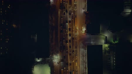 passagem elevada : The camera gradually floats on the night road with slow cars with headlights on. Shooting from a quadrocopter. Lights of the night city beautifully complement the big picture. Movement of cars is fast