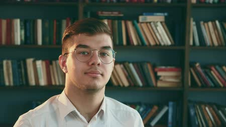архив : A man with glasses is looking at the camera. Student in the university library.