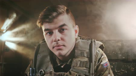 büszke : Portrait of an English military sad man. Fashion Model in camouflage uniforms. Young adult 20s. National patriot in london. Officer for safety. Operation of security in camp. Caucasian ethnicity 4k. Stock mozgókép