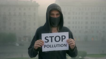 лозунг : Activist breath mask look at camera background city fog with slogan stop pollution. man agitates banner backdrop mist district. People wear the mask. Air pollution. City traffic smog. Man close up.