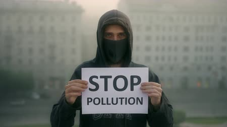 szlogen : People wear the mask. Air pollution. City traffic smog. Activist in breath mask look at camera background city fog with slogan stop pollution 4K. People cannot breathe in country with bad weather