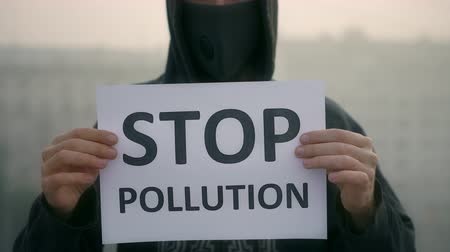 picket : Wear breath mask and protest stand background city smog with message stop air pollution. Man in mask closeup agitate banner mist district. People breathe in country. Stop pollution. Waste emissions 4k Stock Footage