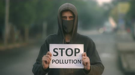 fikirler : Man wear respiratory air mask closeup look at camera background of empty city road in fog. Stop air pollution 4K. Activist people. Breathe in country with bad air and express opinions in mask for smog
