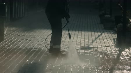 hosing : City worker clean sidewalk with brick block closeup hosing with powerful jet water. People are clearing dirt from city road summer morning 4K. man in working form washes asphalt hosing cleaning agent.