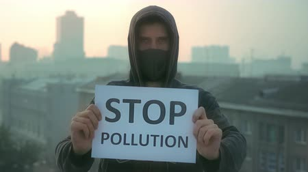 respirator : People wear respiratory mask. Stop air pollution. City traffic smog in air. Man wear respirator. Smog and fog. The environment in city. Banner stop pollution look at camera in city. Protest of people.